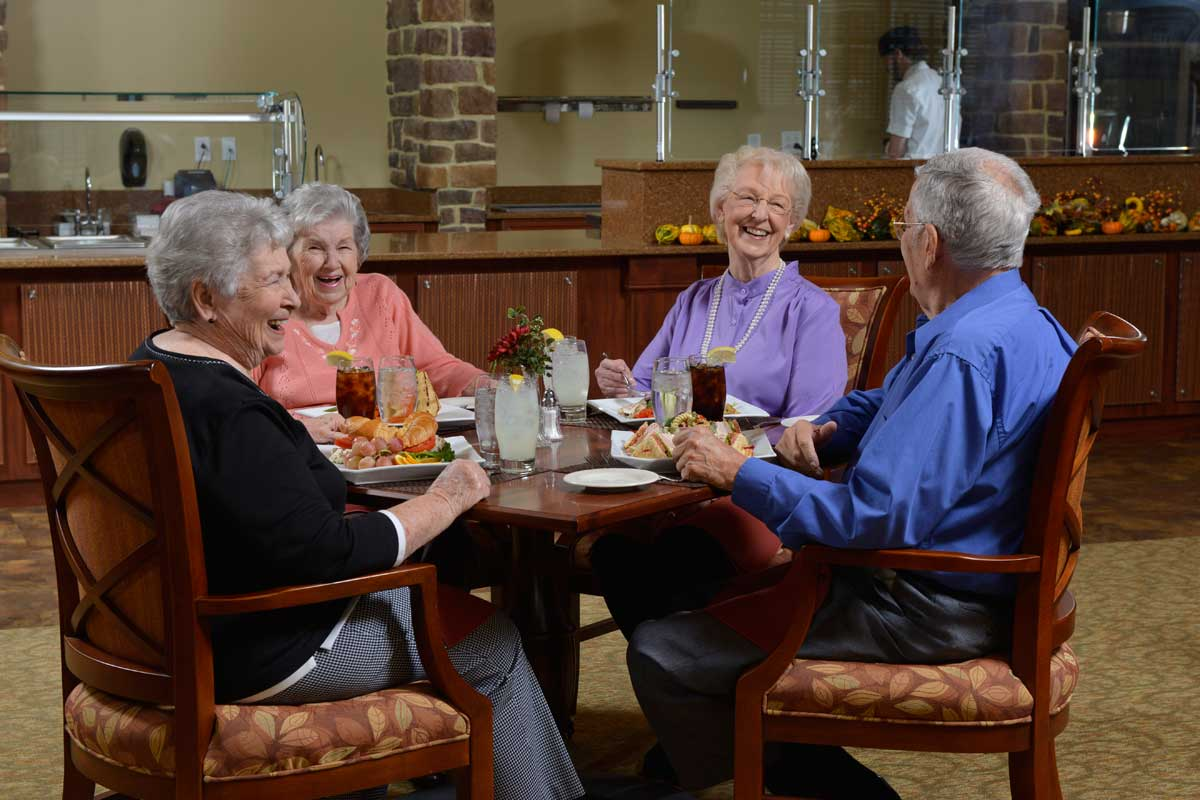 Senior adults laughing and smiling seated at table with meals at Poplar Run