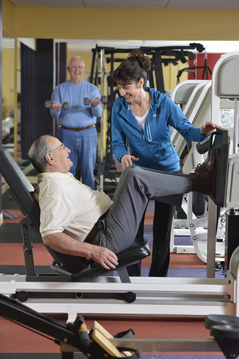 Senior adult men exercising in weight room with trainer at Poplar Run