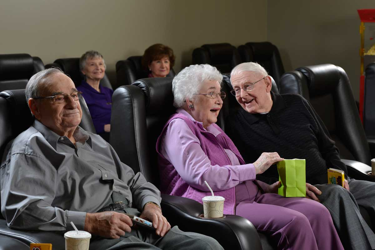 Activities example of senior adults watching a film in theatre seating at Poplar Run